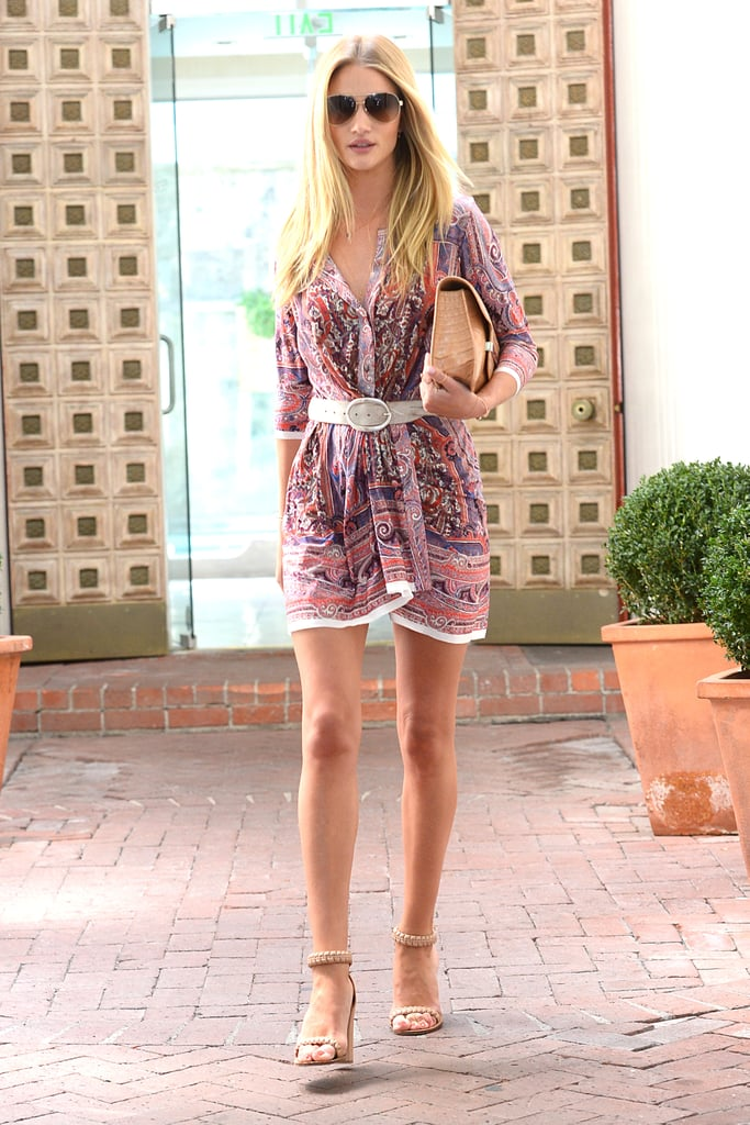 Rosie Huntington-Whiteley strutted out of a hair salon in LA wearing a paisley print mini-dress with neutral add-ons: a white belt, nude ankle-strap sandals, a tan crocodile clutch, and aviator sunglasses.