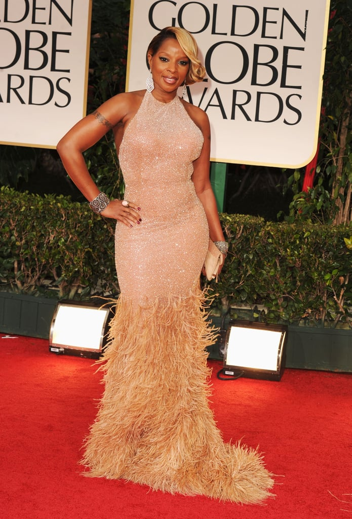 Mary J. Blige wore a shimmery halter gown, embellished with soft feathers down below. Her glamorous gown went perfectly with her clutch, bangles, and soft, wavy hairdo.