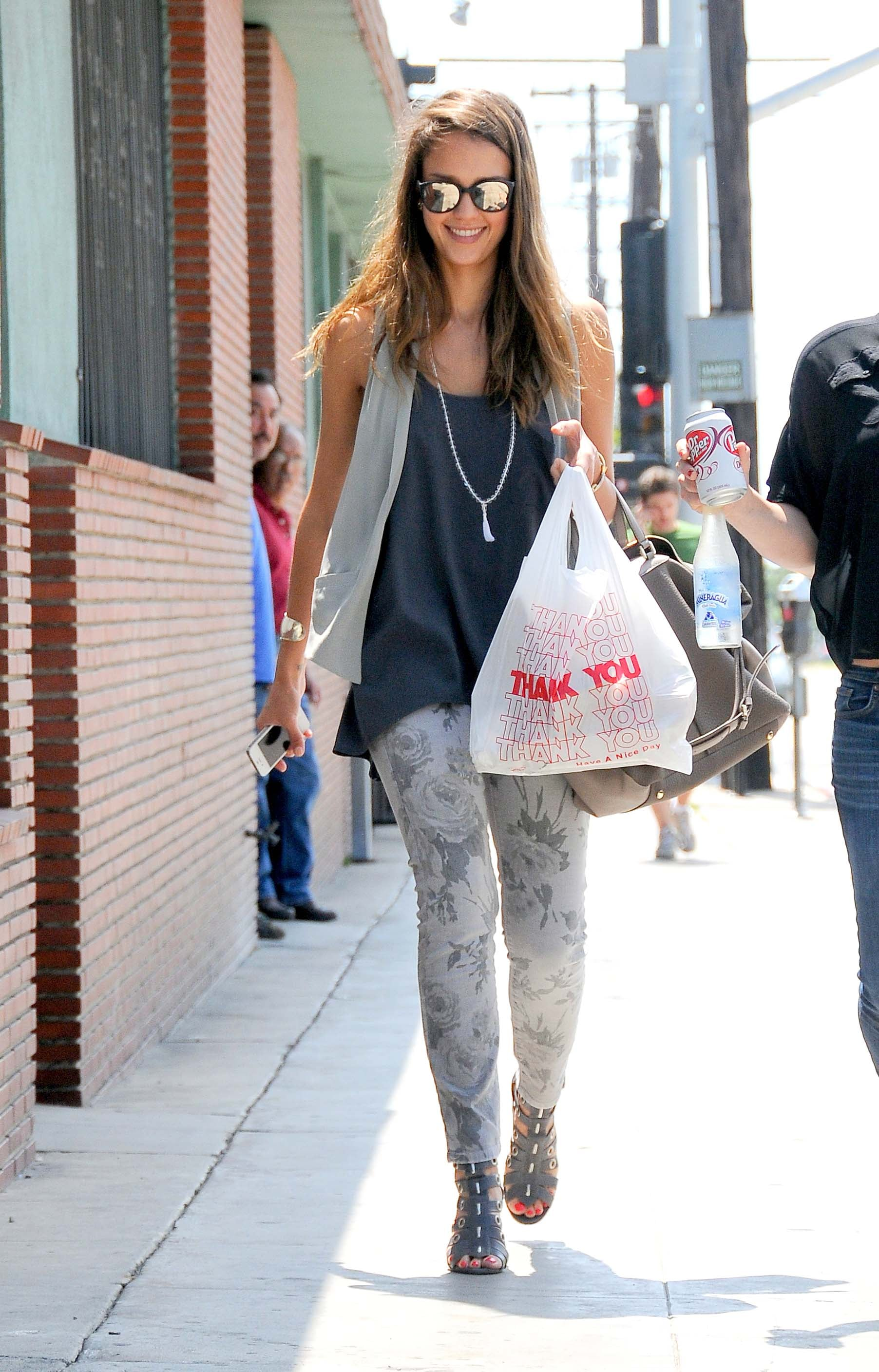 Jessica's neutral Santa Monica style included a gray vest, charcoal silk tank, gray floral Current/Elliott jeans, and matching caged sandals.