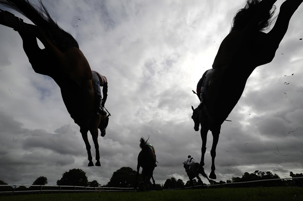 Racehorses jumped over a fence during a steeple chase in Fontwell, West Sussex, England, on Thursday.