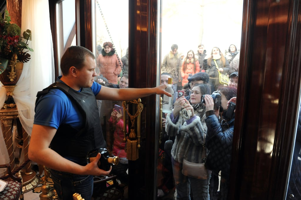 An antigovernment protester held up a bottle of liquor for people to photograph from the outside.