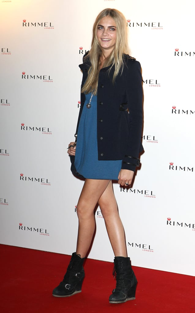 Cara Delevigne's adds edge to a minidress with wedged biker boots and a dark Fall topper.