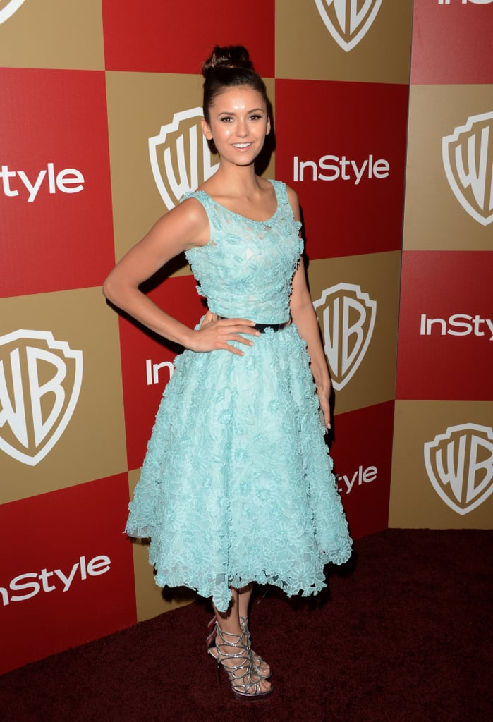 At the InStyle party, Nina Dobrev showed off her flirty sense of style via a full-skirted ladylike look, punched up by a powder blue hue and an embellished texture. Her high bun, glowing makeup, and strappy heels rounded out her look.
