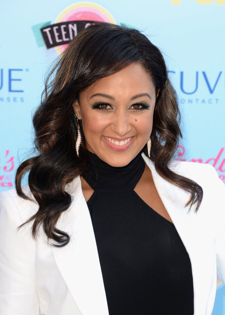 Black liner, gilded lids, and chestnut waves were Tamera Mowry's look du jour.