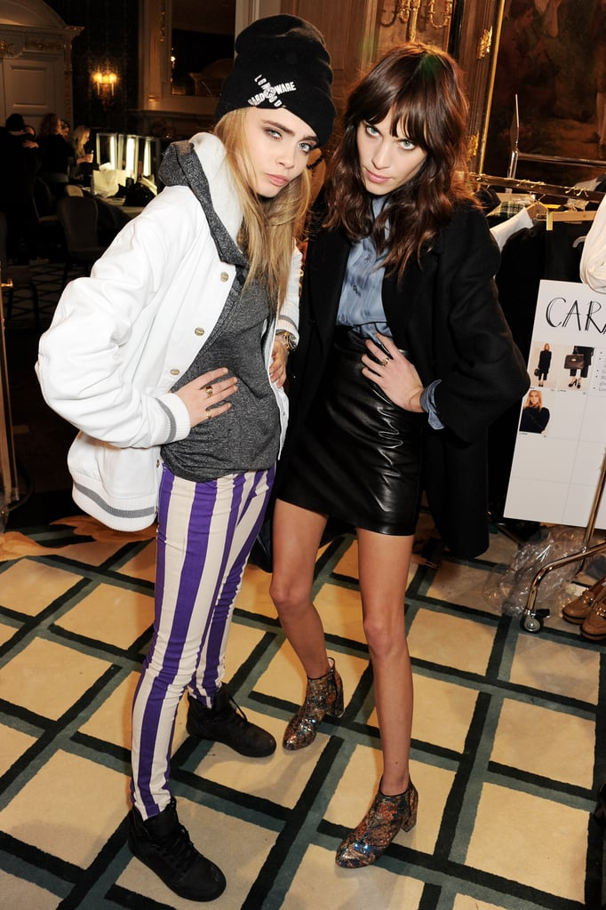 Cara Delevingne, clad in funky striped jeans, and Alexa Chung in a leather skirt, fooled around backstage at Mulberry.