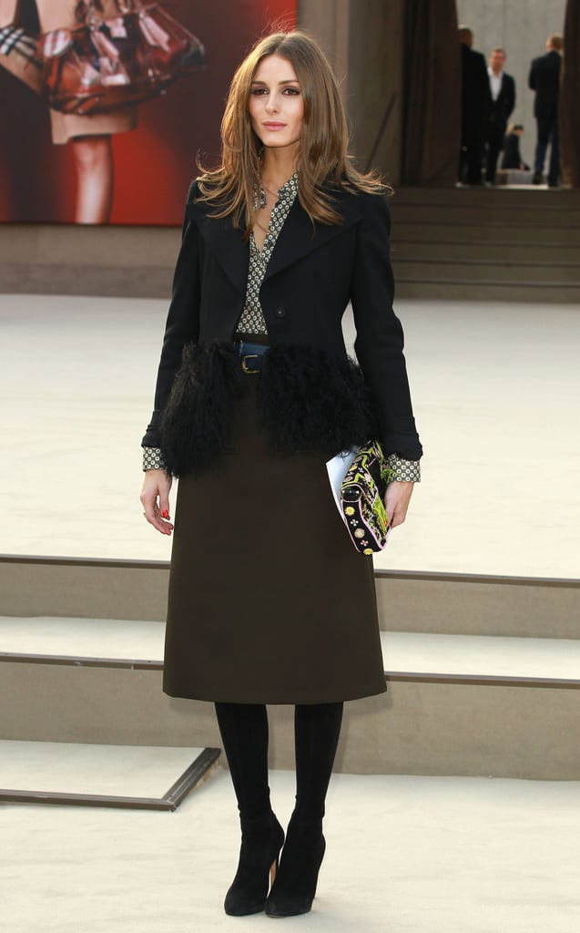 Olivia Palermo worked ladylike with a twist in a knee-length olive skirt, a printed blouse, black shearling blazer, and a funky printed clutch at Burberry.