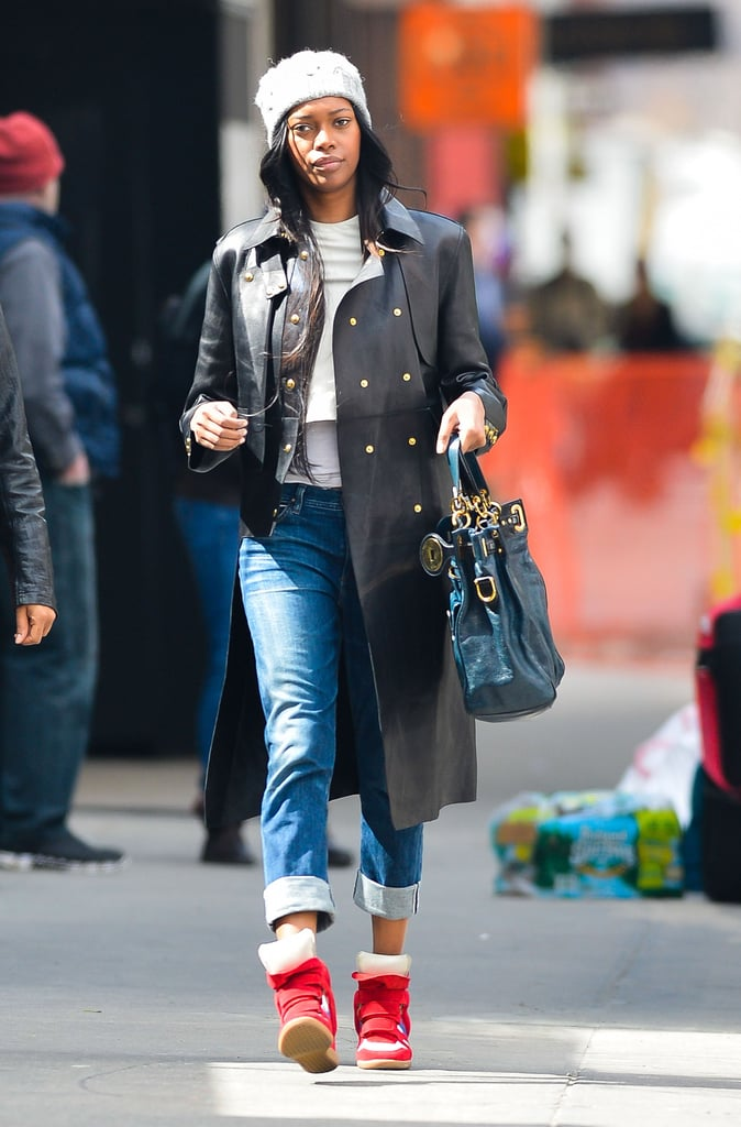 Jessica White got funky during an NYC stroll in a black leather military-style coat, red wedge sneakers, and a knit beanie.