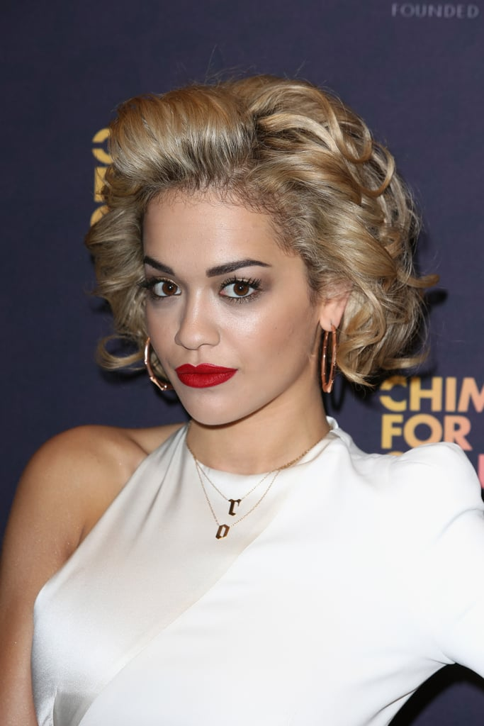 Platinum blond curls and fire-engine red lipstick are fast becoming Rita Ora's signature beauty combination.