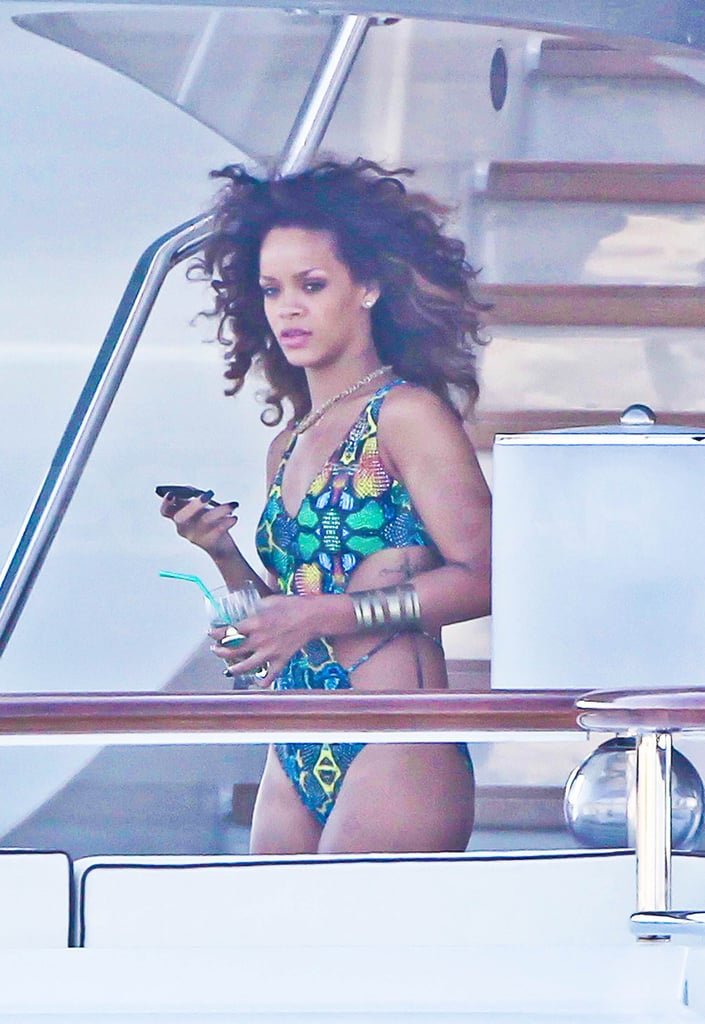 Rihanna checked her phone and sipped on a cocktail.