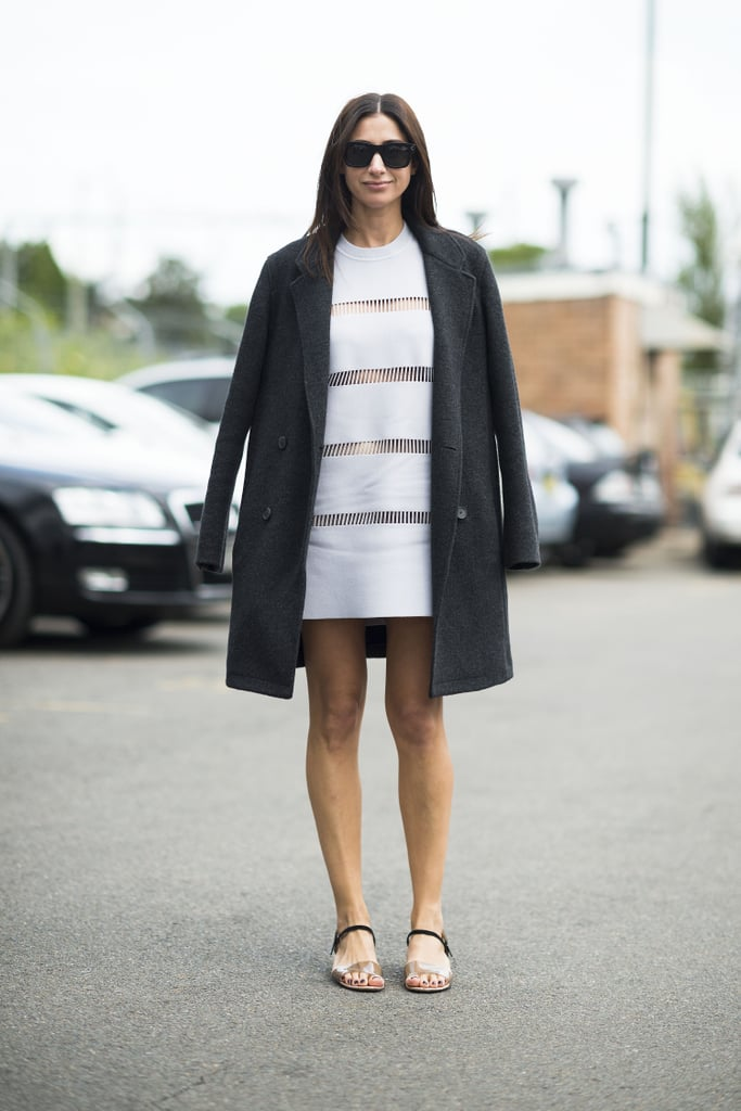 This showgoer grounded a stem-baring LWD with a coat, then finished it off with easy sandals. Source: Le 21ème | Adam Katz Sinding