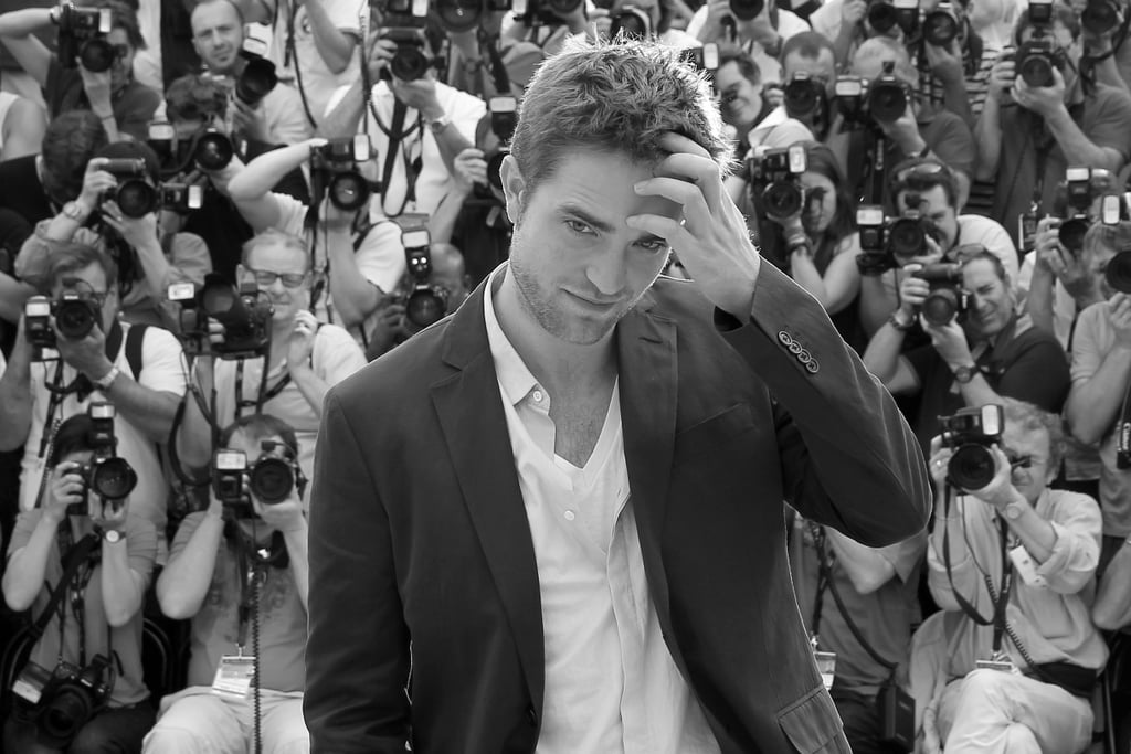 Robert Pattinson combed his hand through his hair at the Cosmopolis photocall in Cannes.