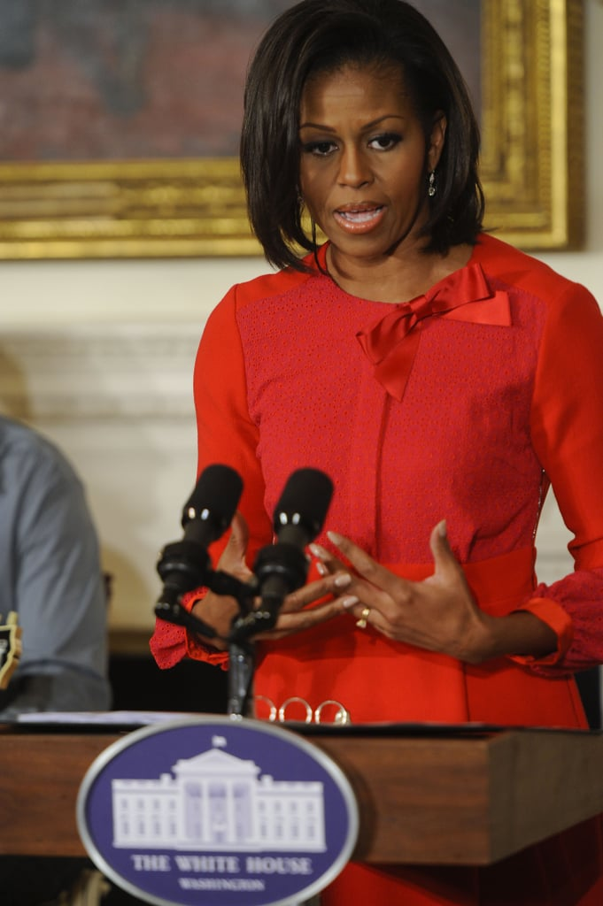 To deliver a speech on the history of music and dance, the FLOTUS wore a red jacket-and-skirt combo. The side-bow detail on the jacket neckline is sweet and playful.