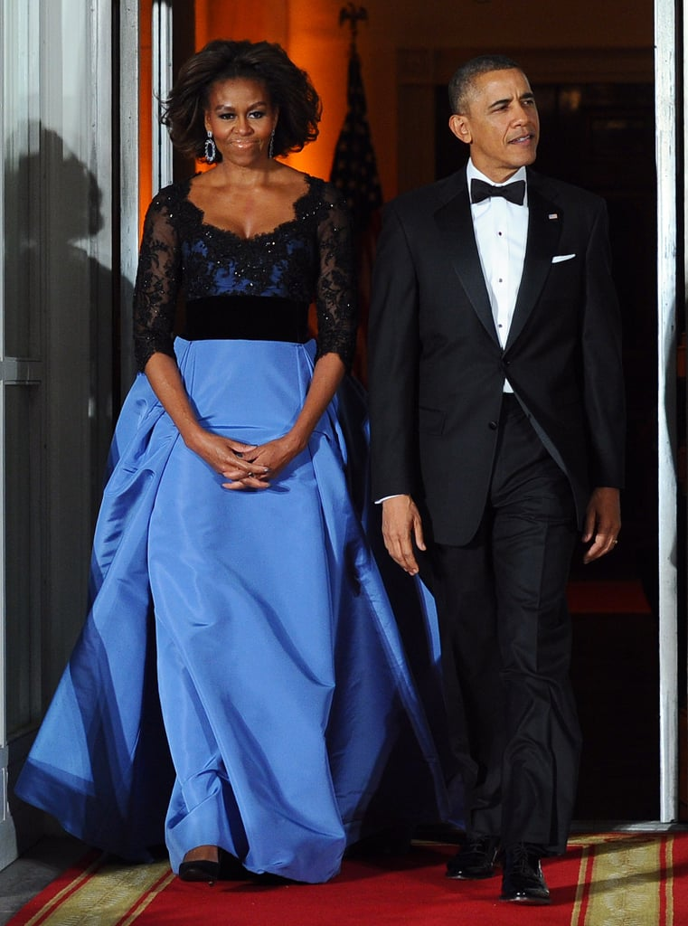 Très chic! To greet French President Francois Hollande, the first lady made a fittingly sophisticated choice of a beaded liberty blue silk faille Carolina Herrera design that she paired with coordinating Sutra earrings.
