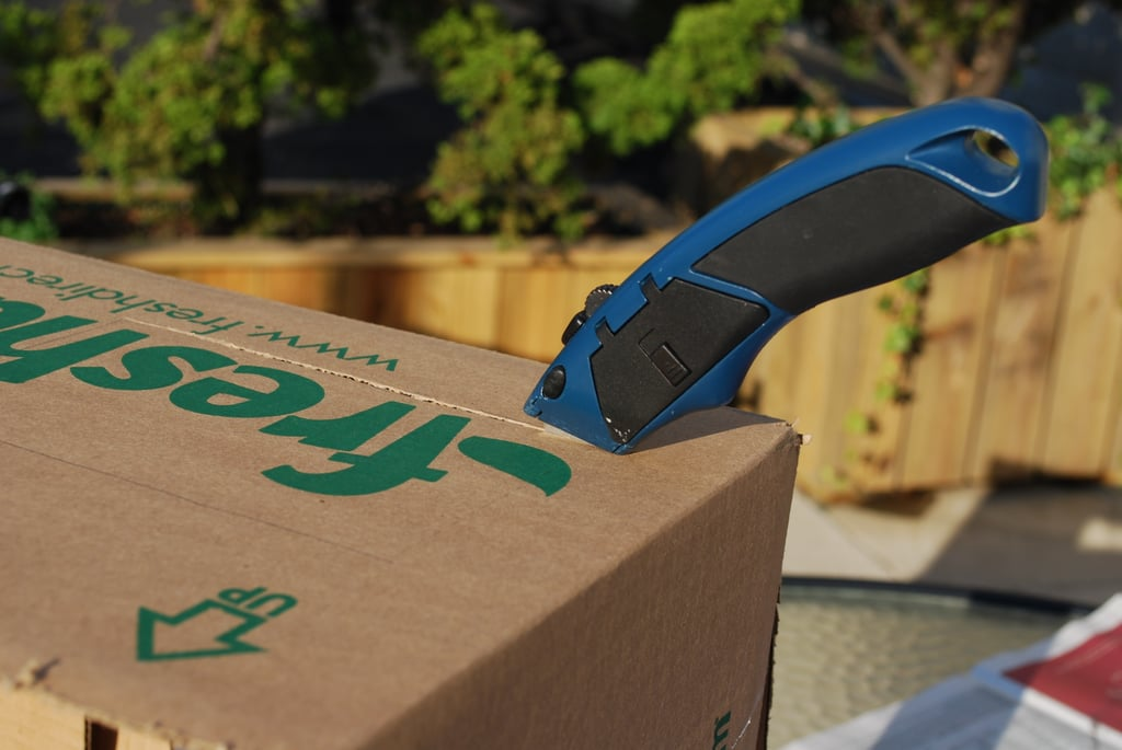 Using your box cutter, cut out some small holes on either side of the box that will become arm-holes.