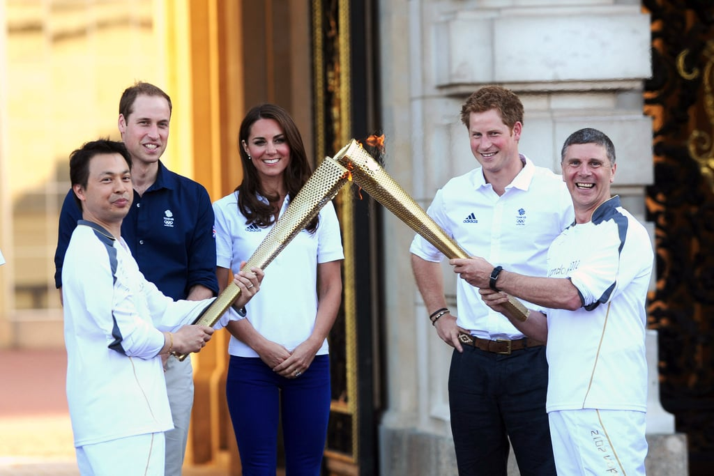 Prince William, Kate Middleton and Prince Harry watched a handover of the Olympic flame at Buckingham Palace in London on July 26.