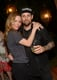 Leslie wrapped her arm around Joel Madden as the two caught up.
