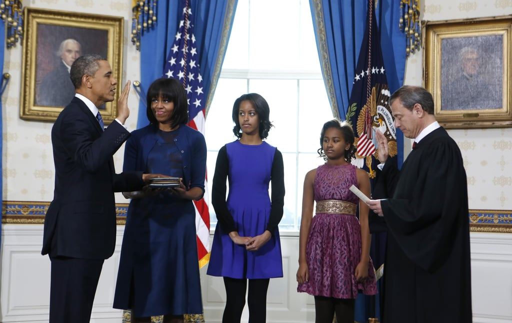 For the Sunday swearing-in ceremony held in the Blue Room of the White House, Michelle Obama chose the color du jour: blue. Wearing a printed Reed Krakoff sheath with a solid-hued cardigan and low black heels, Michelle looked every bit the polished FLOTUS. Meanwhile, her older daughter, Malia, layered a black long-sleeved top under a cobalt H&M dress, and Sasha wore a purple lace confection by Plenty by Tracy Reese.