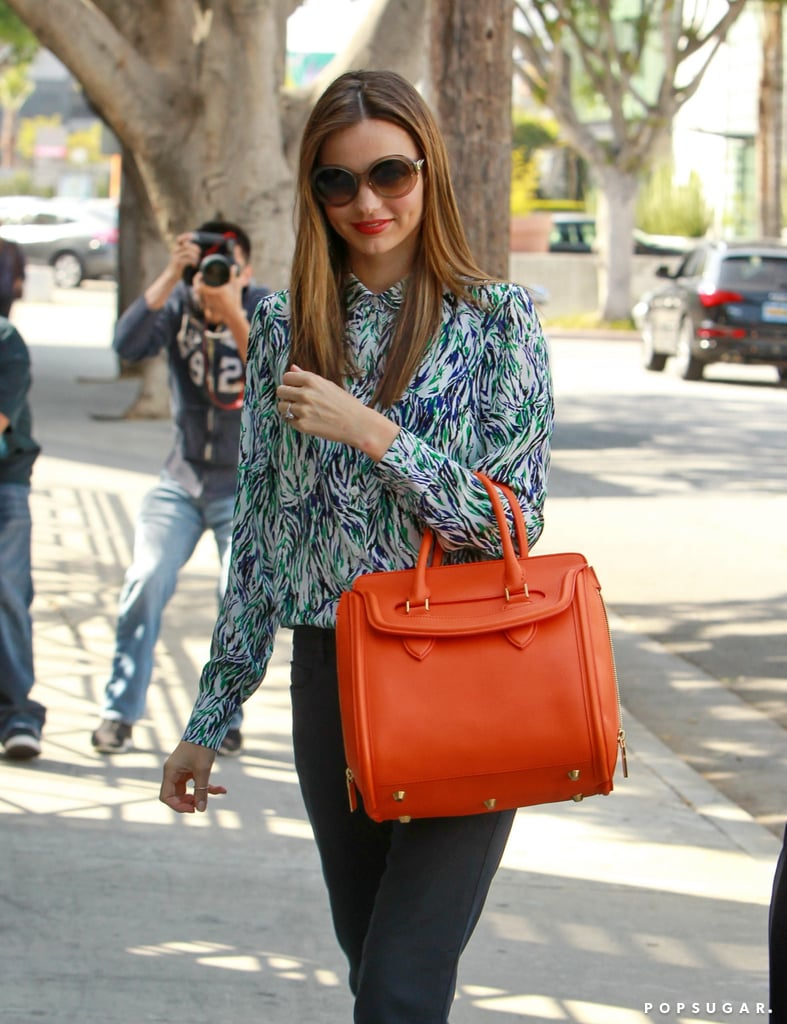 Miranda Kerr carried a bright orange bag.