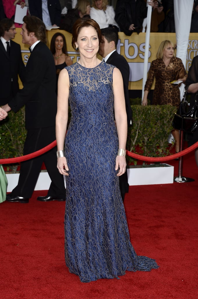 Edie Falco accessorised her navy lace overlay gown with wide silver cuffs and sapphire earrings.