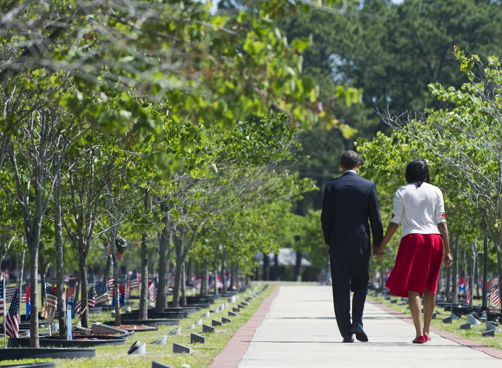 The president and the first lady held hands as they walked along a path.