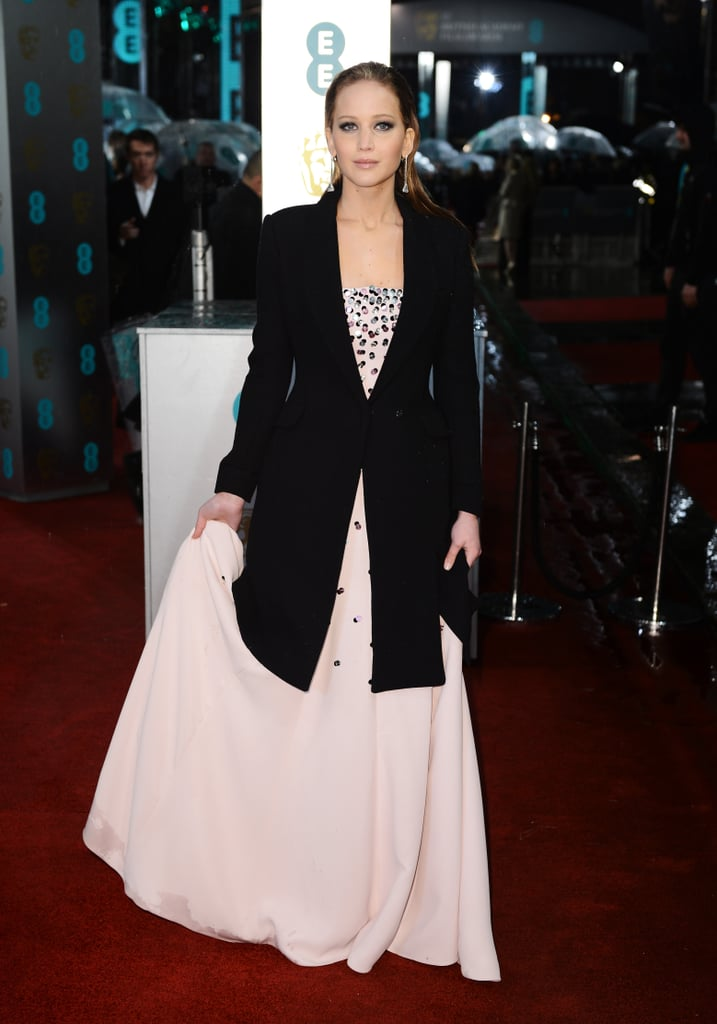 Jennifer Lawrence covered her Dior gown with an overcoat.