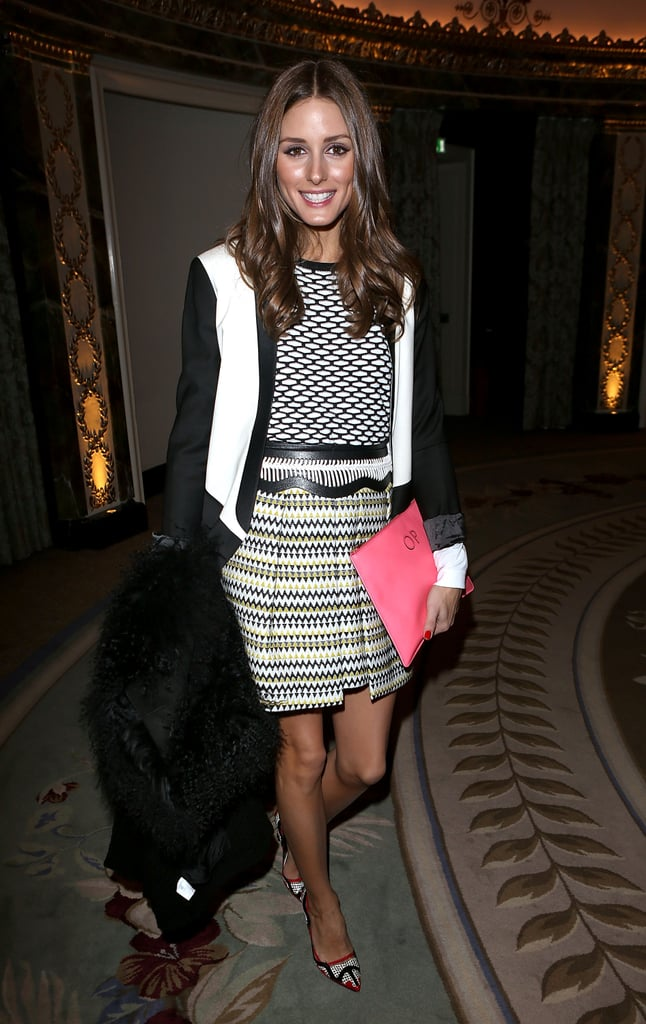Olivia mixed prints like a pro in a geometric-print sweater, pleated Milly skirt, colour-blocked Tibi blazer, and red-trim pumps at the Temperley London show in London.