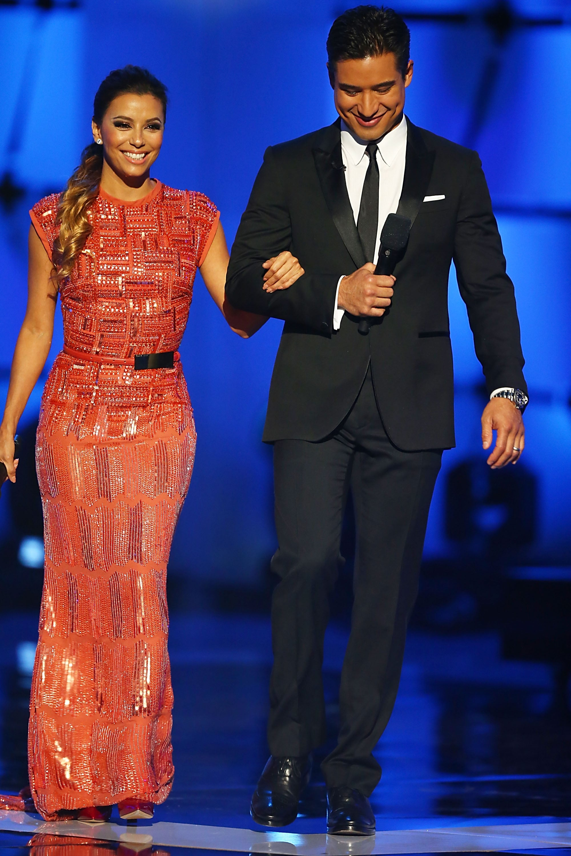 While making an appearance on stage with Mario Lopez, Eva glistened in an embellished coral Elie Saab gown.