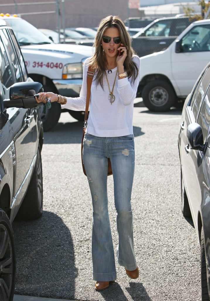 Alessandra picked a pair of light denim flares and a thin white top for an early Winter day in LA.