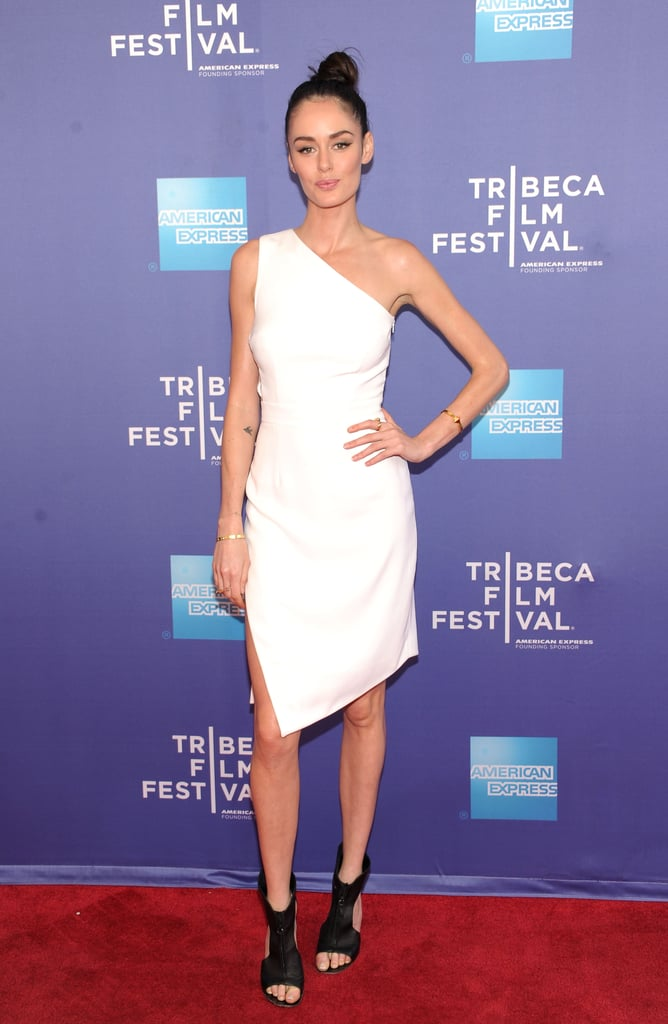 At the HBO premiere of The Battle of AmfAR, Nicole Trunfio's white one-shouldered dress featured an asymmetrical hemline that gave it a unique twist. Her black cutout booties lent further edge.