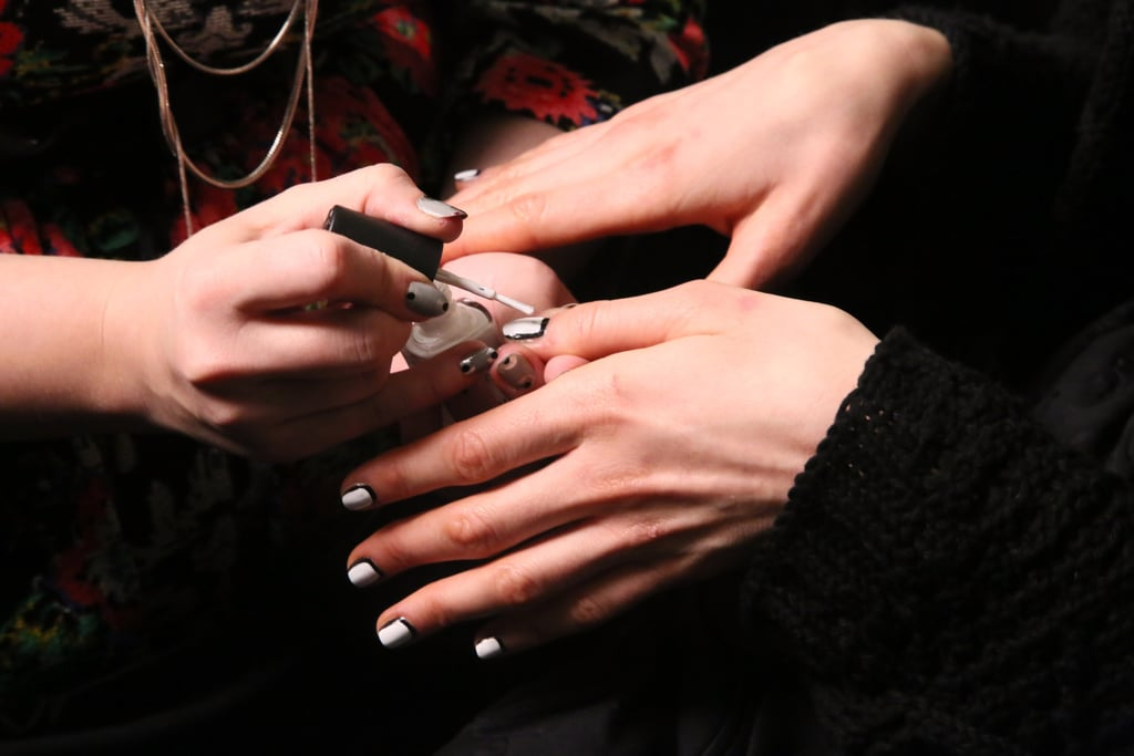 """The nails were designed by Simcha Whitehill for Color Club. She brought to life a """"picture frame"""" manicure for a simple and graphic result. To create the look, she painted the base colour first (in this case, the black shade first). Then she painted the centre white, leaving the perimeter black."""