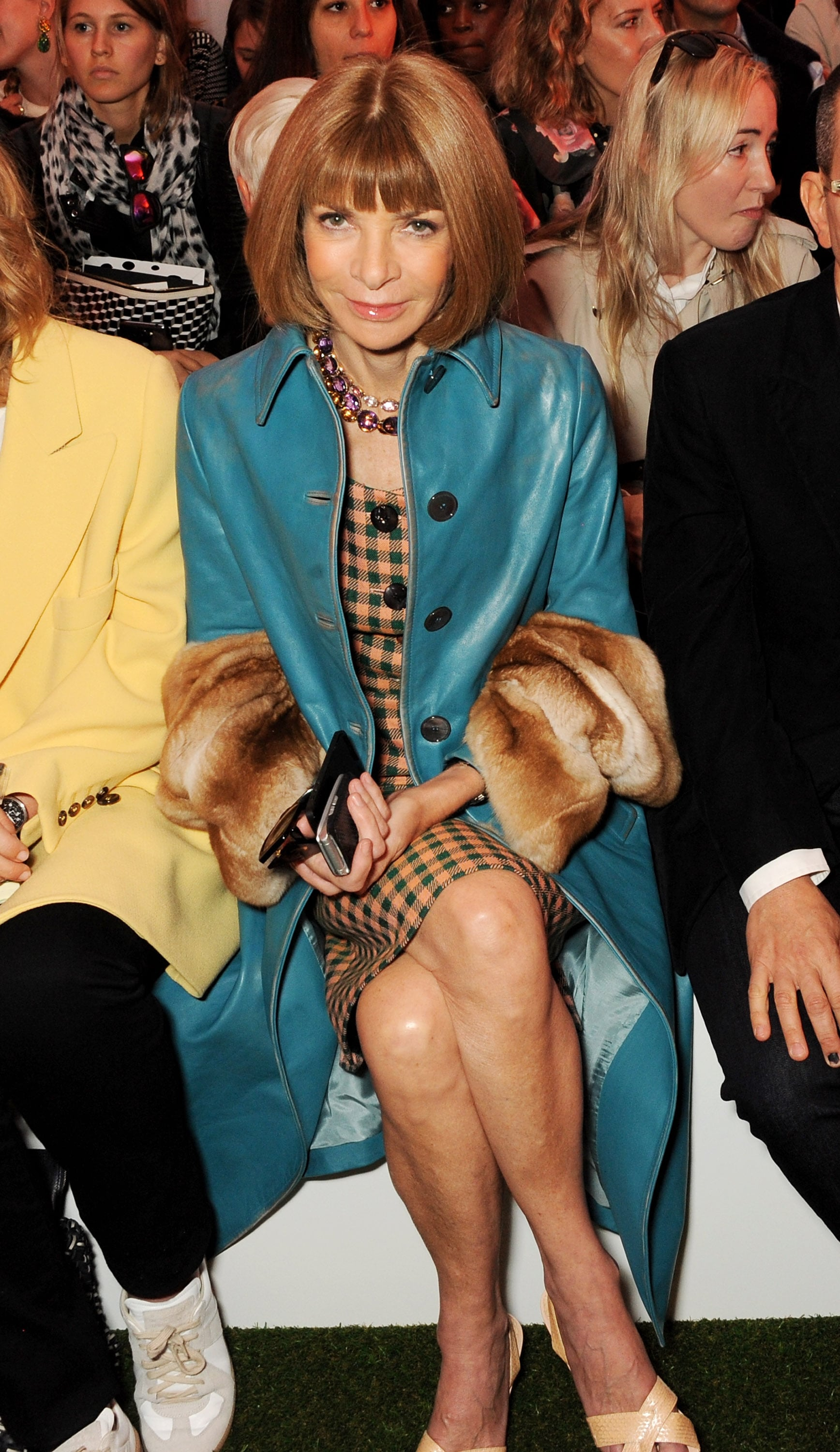 Anna Wintour accented her Fall-ready dress with a fur-trimmed teal topper at the Mulberry show.