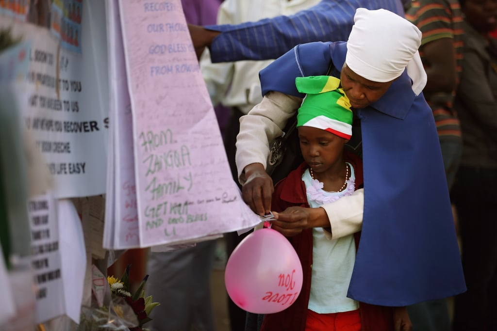 A child and her grandmother attached a balloon to the memorial wall outside the hospital.