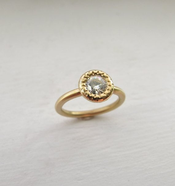 We like the juxtaposition between the organic raw stone and polished gold.  8kt Gold and Moissanite Raw Circle Solitaire Ring ($880)