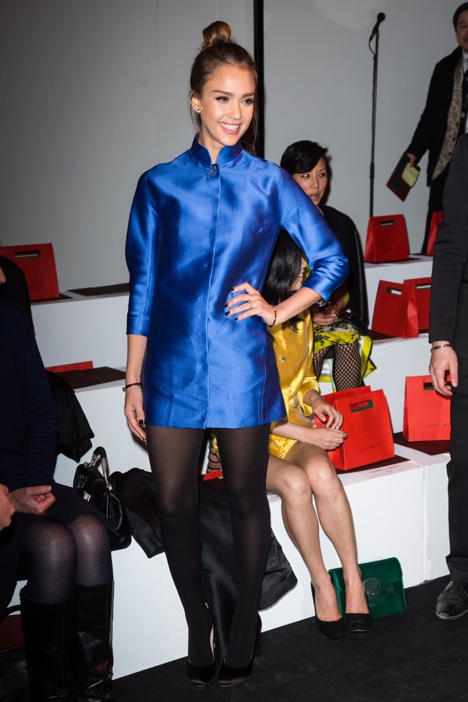Jessica Alba stopped by the Shiatzy Chen show at PFW in a silky cobalt coat dress with a mock collar, black tights, and satin pumps.