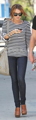 Miley Cyrus Wears Stripes Shirt and Clogs with Balenciaga Bag
