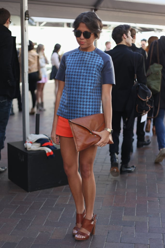 Look to this chic ensemble for sophisticated Summer styling cues. Her boxy blue houndstooth top got an extra boost courtesy of her bold orange shorts — a fun color combo we've been loving lately.