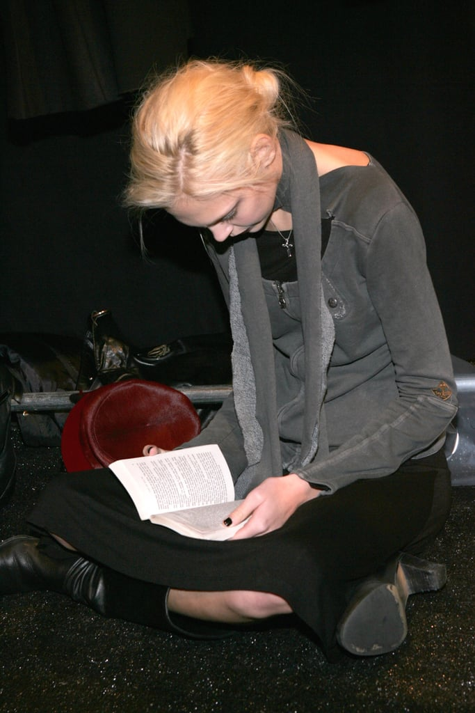A cross-legged model read a book backstage at the Alice Roi Fall 2006 fashion show during New York Fashion Week.