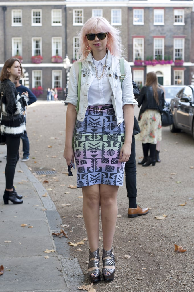 We're having a '90s flashback via her denim jacket, multicolored printed skirt, and silver metallic wedges.