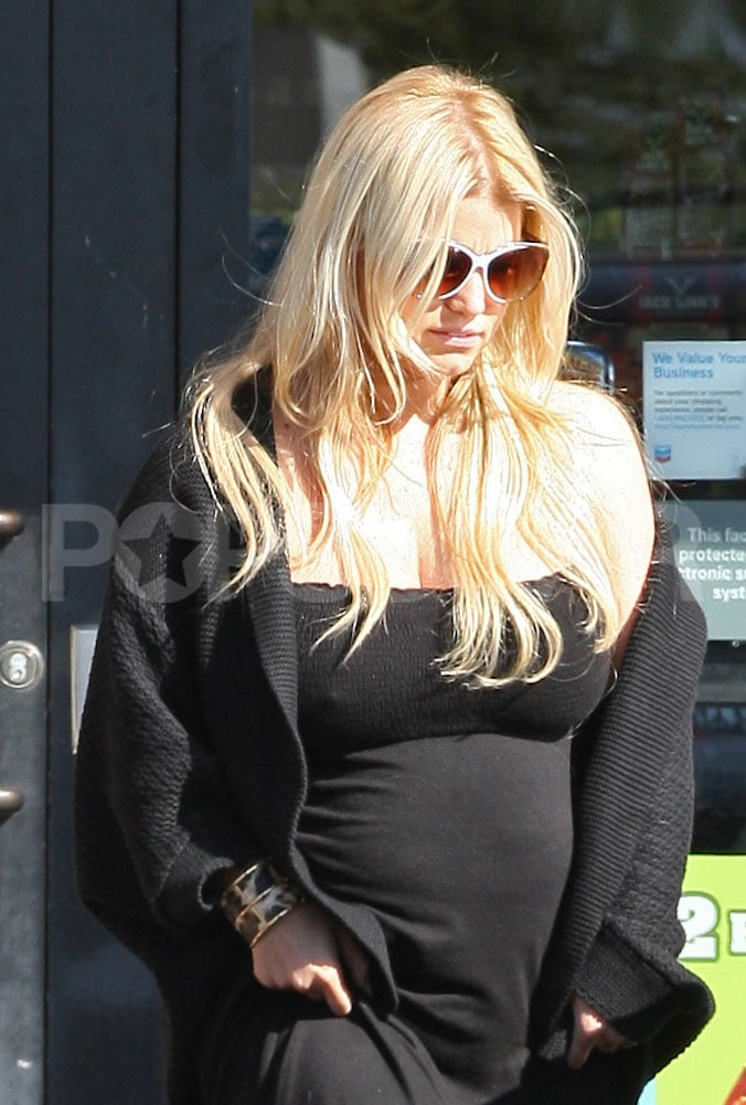 Jessica Simpson looking pregnant in black dress.