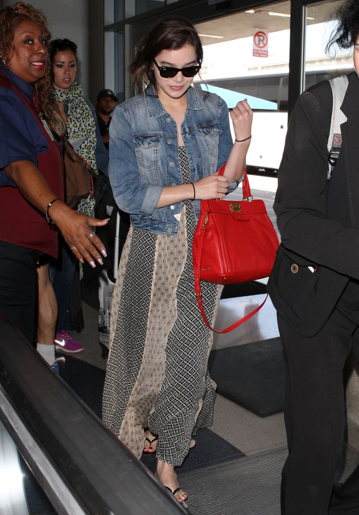 Jazz up your maxi dresses with a denim jacket and a bold bag like Hailee Steinfeld did during her Summer travels.