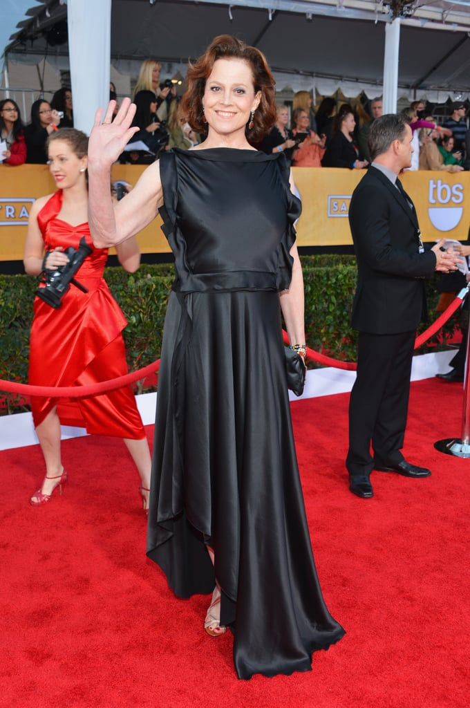 Sigourney Weaver donned a black ruffle-detailed satin gown with strappy gold sandals.