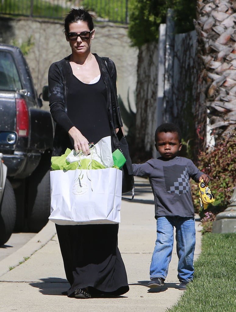 Sandra Bullock took little Louis by the hand on the way to Charlize Theron's Beverly Hills home for her son Jackson's birthday party on Sunday.