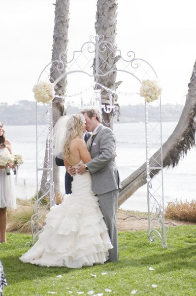 Against a gorgeous view, a simple white archway helps you and the scenery stand out. Photo by Angie Silvy Photography via Style Me Pretty