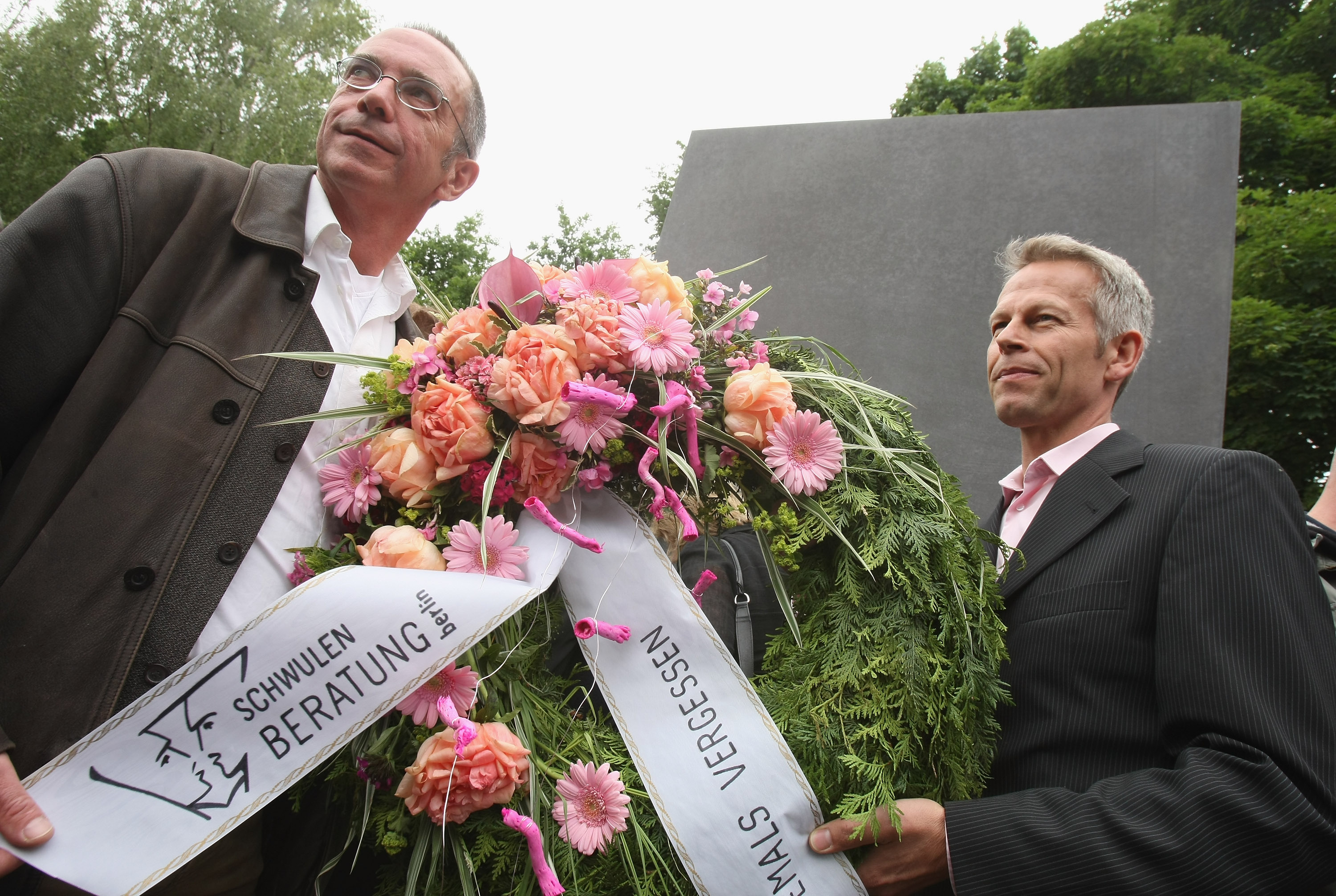 Two men from a gay counseling organization hold a wreath.