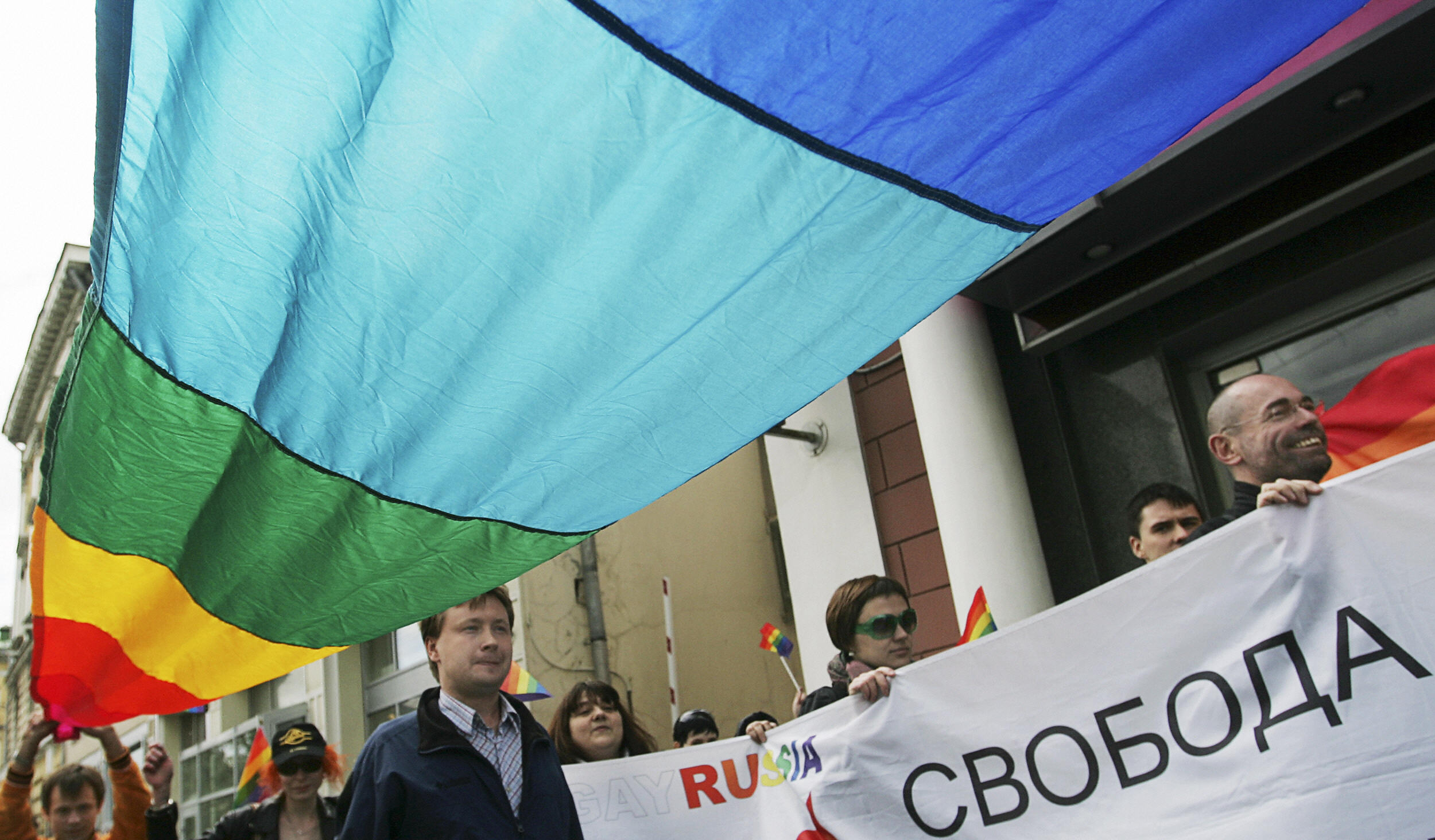 Members of the Russian gay community hold flags.