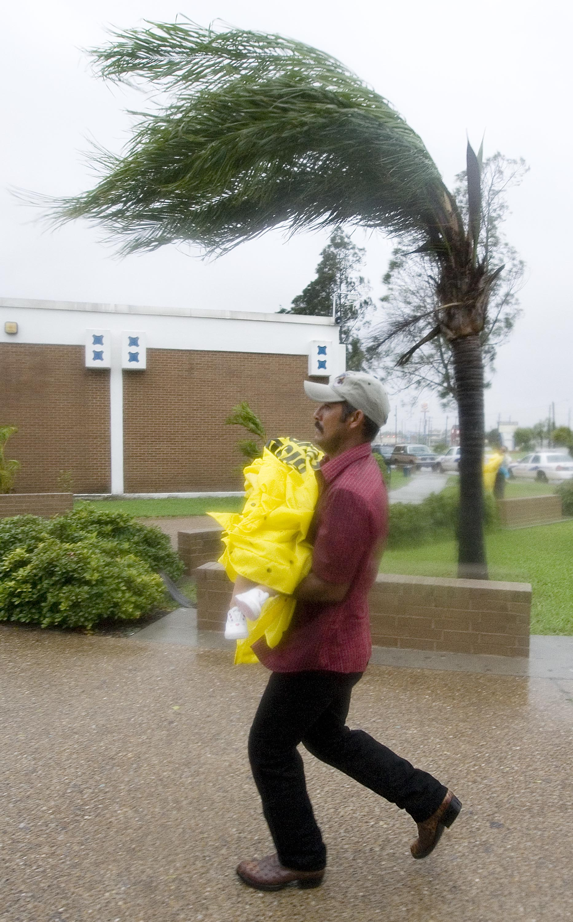 Evacuee runs with his bundled up daughter to a shelter.