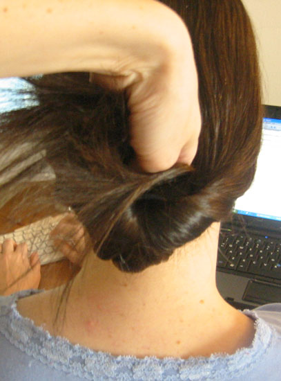 Lift ponytail up and over ponytail holder, right into the hole you created. Push all the way through.
