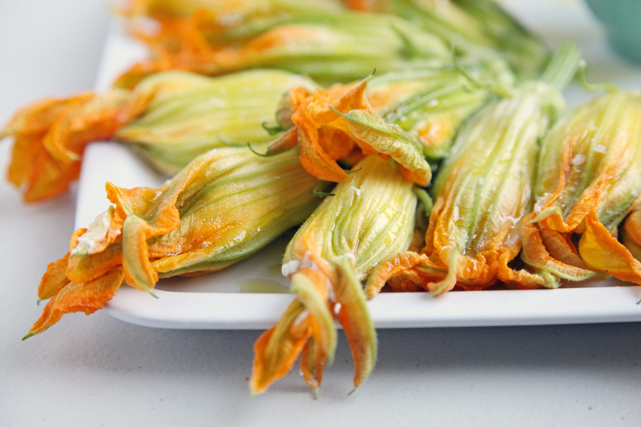 PopsugarLivingSummerBurrata-Stuffed Squash Blossom RecipeKiller App: Burrata-Stuffed Squash Blossoms With Olive TapenadeAugust 24, 2012 by Nicole Perry920 SharesChat with us on Facebook Messenger. Learn what's trending across POPSUGAR.Traditionally, squash blossoms are stuffed with creamy cheese, battered, and deep fried; lovely and enticing in their own right, to be sure, but a girl can only eat so many deep-fried snacks without palate fatigue. So when my best friend brought a basket of these Summer beauties to dinner, alongside a rustic baguette, a tub of creamy burrata, and a jar of pungent olive tapenade, I knew I was in for a real treat.I watched in rapt attention as she deftly prepared this quick appetizer, barely able to restrain myself from sneaking a taste of the burrata as it oozed with cream. Mere minutes later, we bit in, and at that moment, I was sold. Not only are squash blossoms extraordinarily beautiful in their raw state, but when shed of their battered exterior, their nuanced delicate flavor - 웹