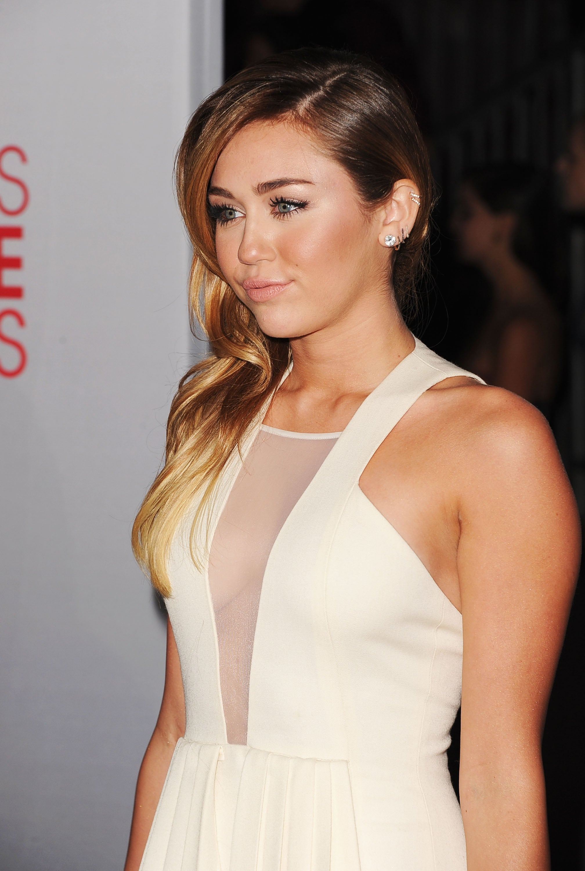 Miley Cyrus pushed her hair to one side.
