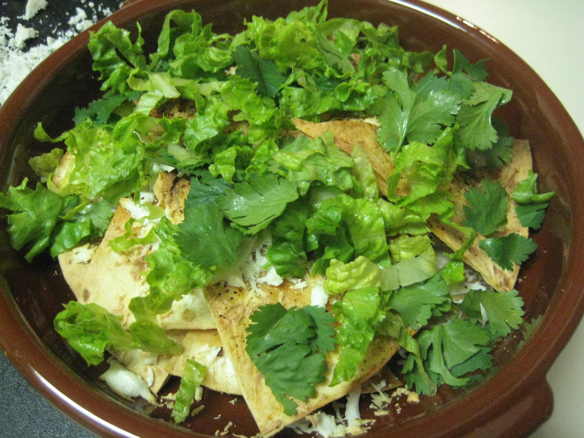 Topping with lettuce and cilantro.